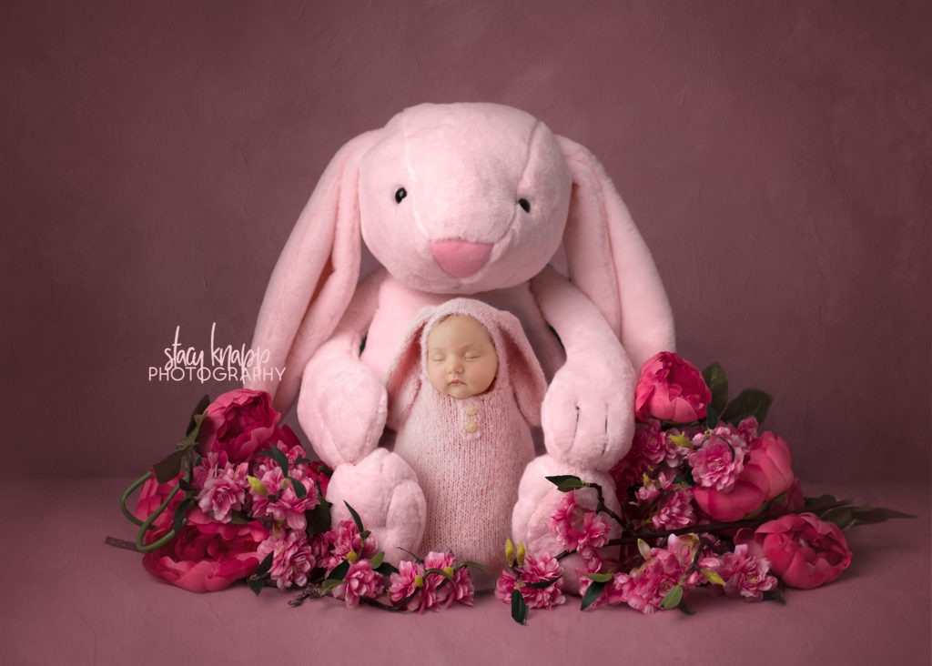Newborn photograph of a baby girl in a soft pink bunny outfit