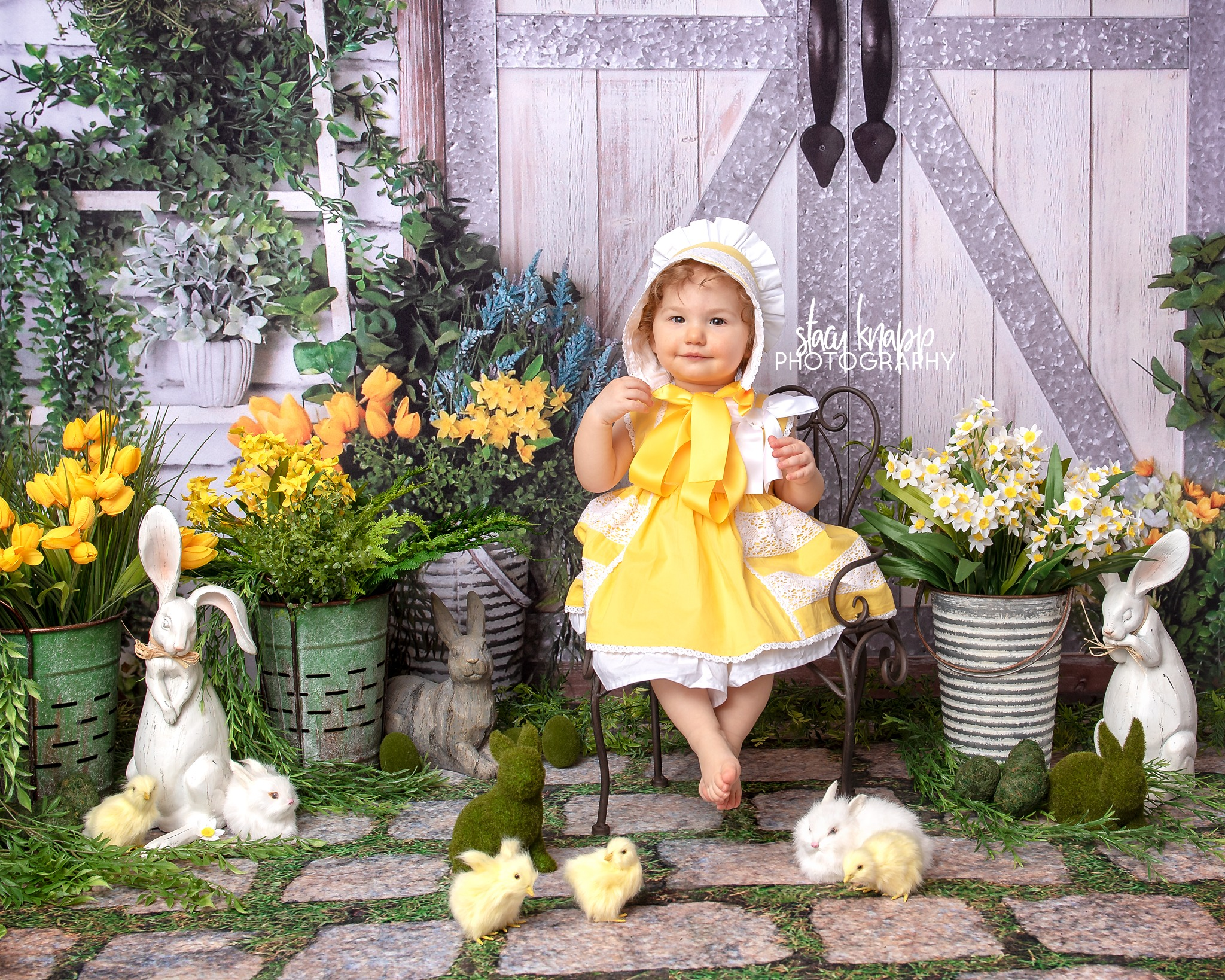 Spring mini session photograph of a baby girl in adorable yellow dress and matching bonnet