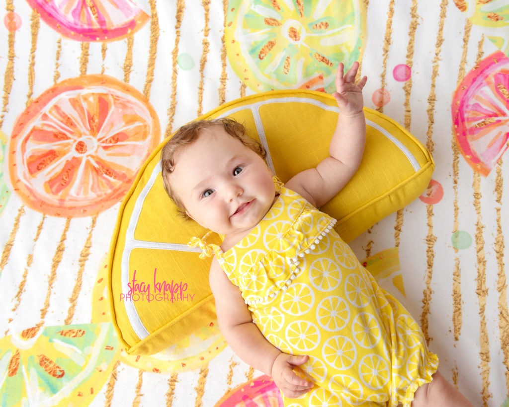 Baby girl photographed wearing lemon outfit on citrus backdrop