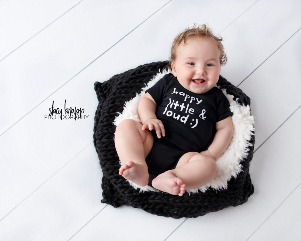 Baby girl photographed in black little and loud onesie on white wood backdrop