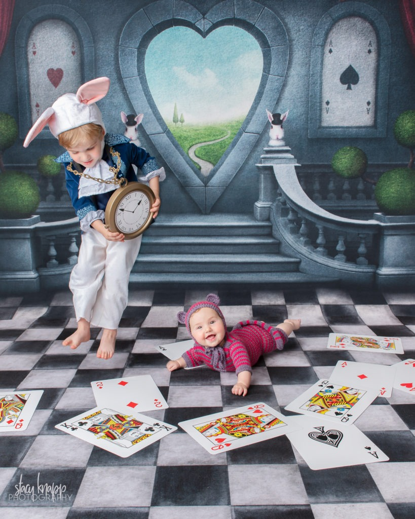 Brother and sister photographed on Alice in Wonderland backdrop