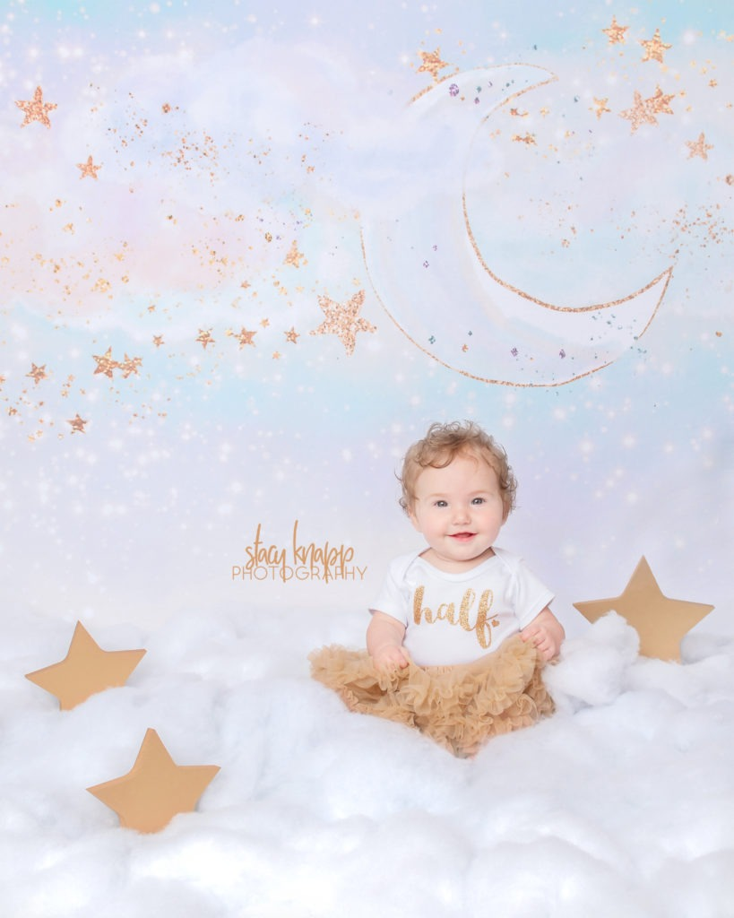 Six-month-old (half year) baby girl photographed in cloud scene with gold tutu