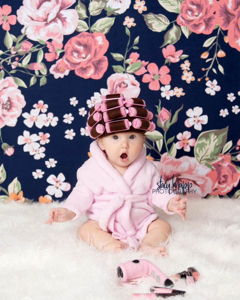 Baby girl photographed in hair curlers and a bathrobe