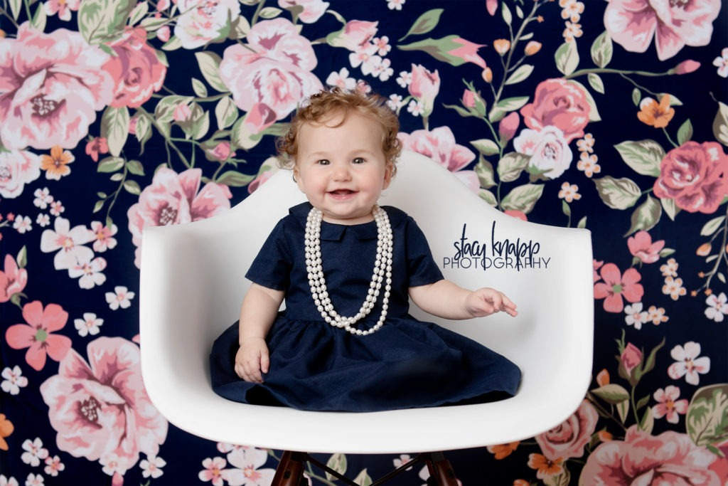 Baby girl photographed in navy blue dress with pearls on a navy blue floral backdrop