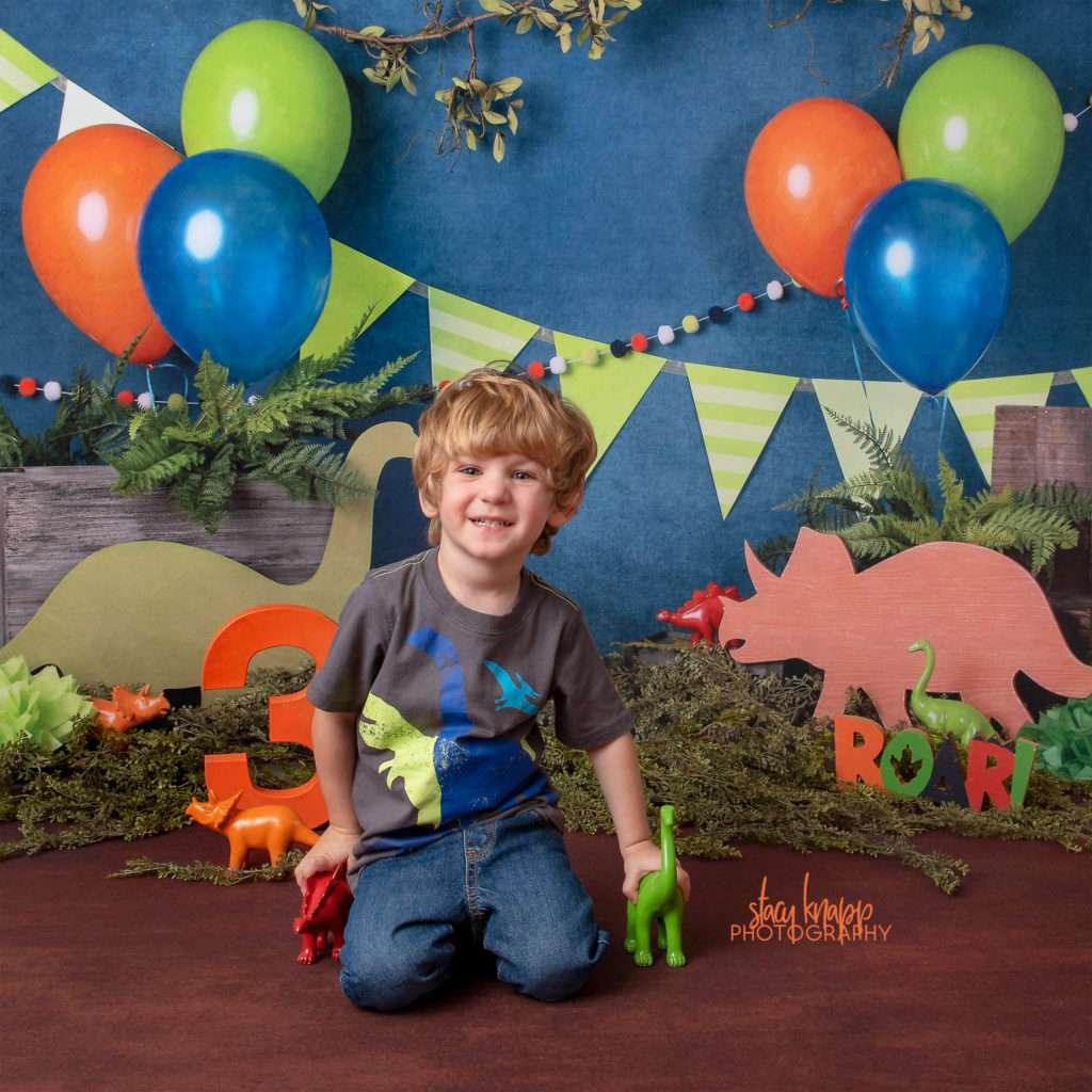 Preschool boy age three photographed on dinosaur backdrop