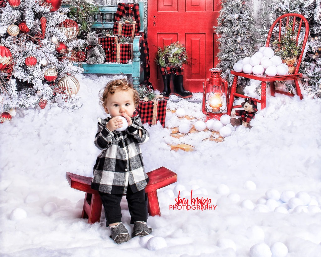 Baby girl Christmas holiday photo wearing black and white plaid with finger in her mouth