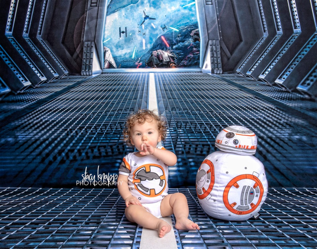 Baby girl photographed on Star Wars backdrop wearing BB8 outfit