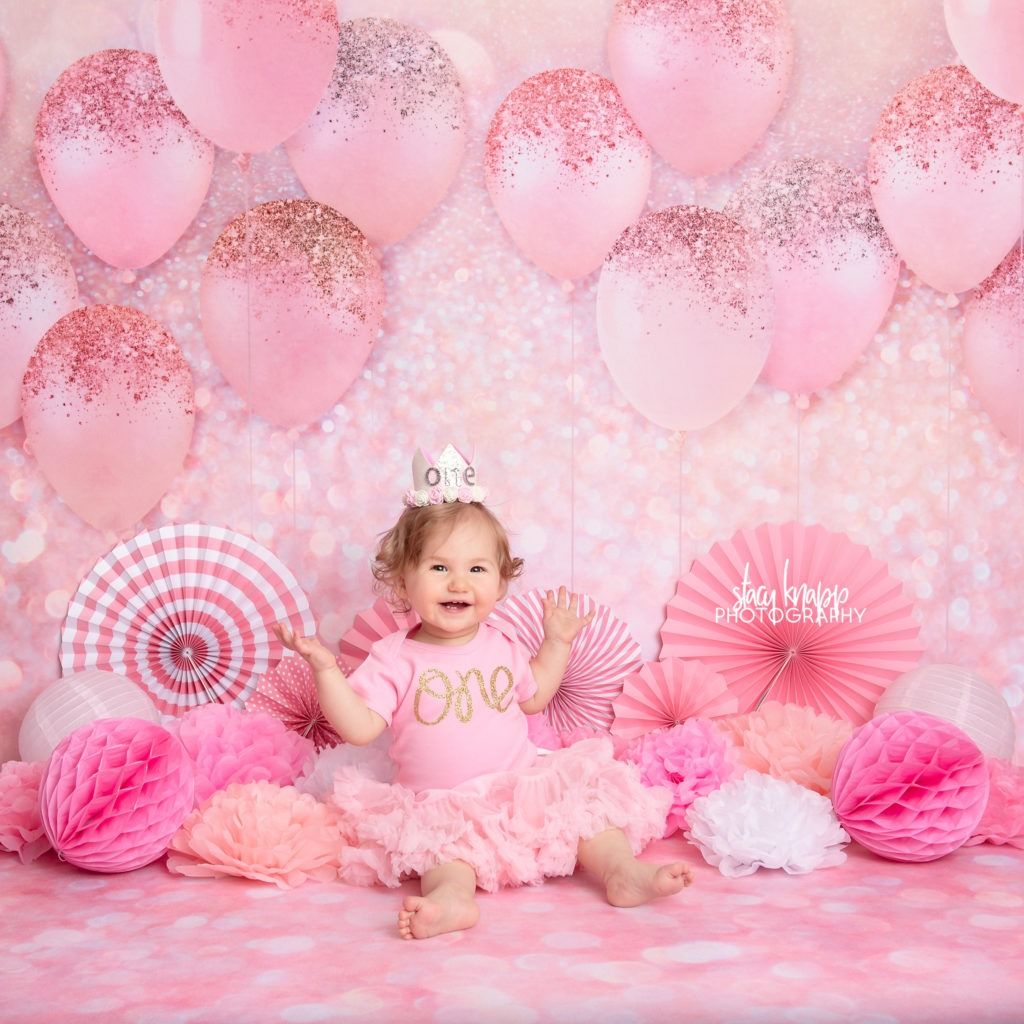 One-year-old baby girl photographed on pink balloon backdrop during birthday milestone session