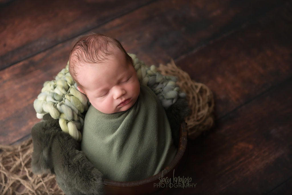 Newborn photograph of a baby boy wrapped in green in a brown wood bucket