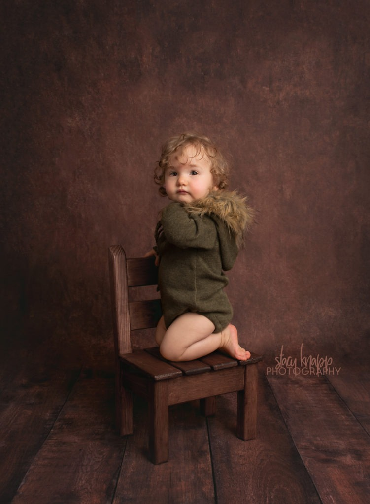 Photo of toddler girl in green fuzzy hood outfit on dark wood backdrop