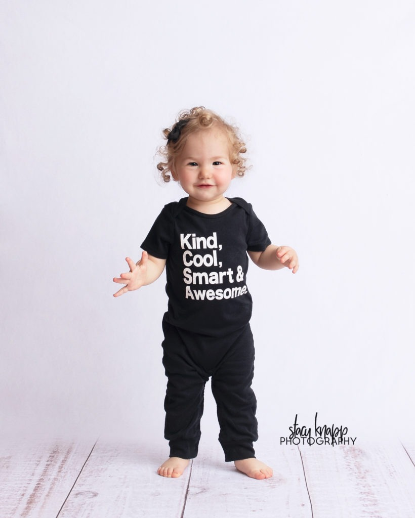Toddler baby girl on white wood backdrop wearing kind cool smart and awesome outfit