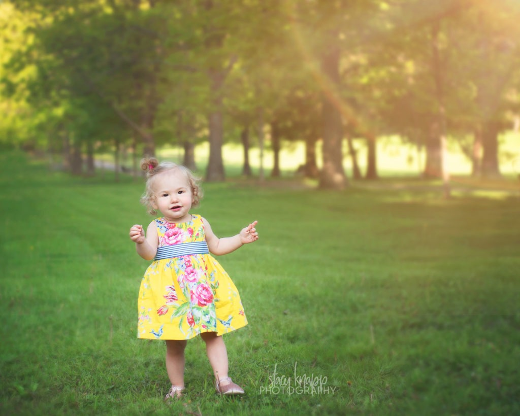 Toddler girl in Capital Park in Augusta, Maine walking in grass wearing yellow floral dress