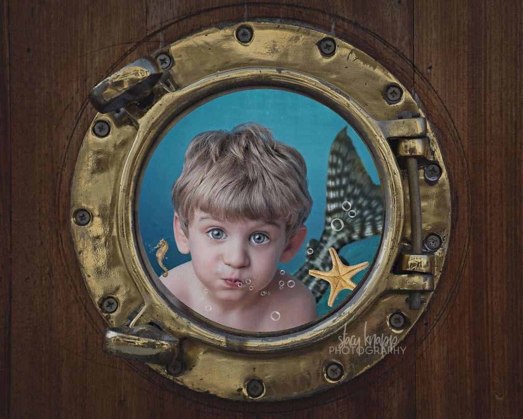 Little boy as mermaid at porthole