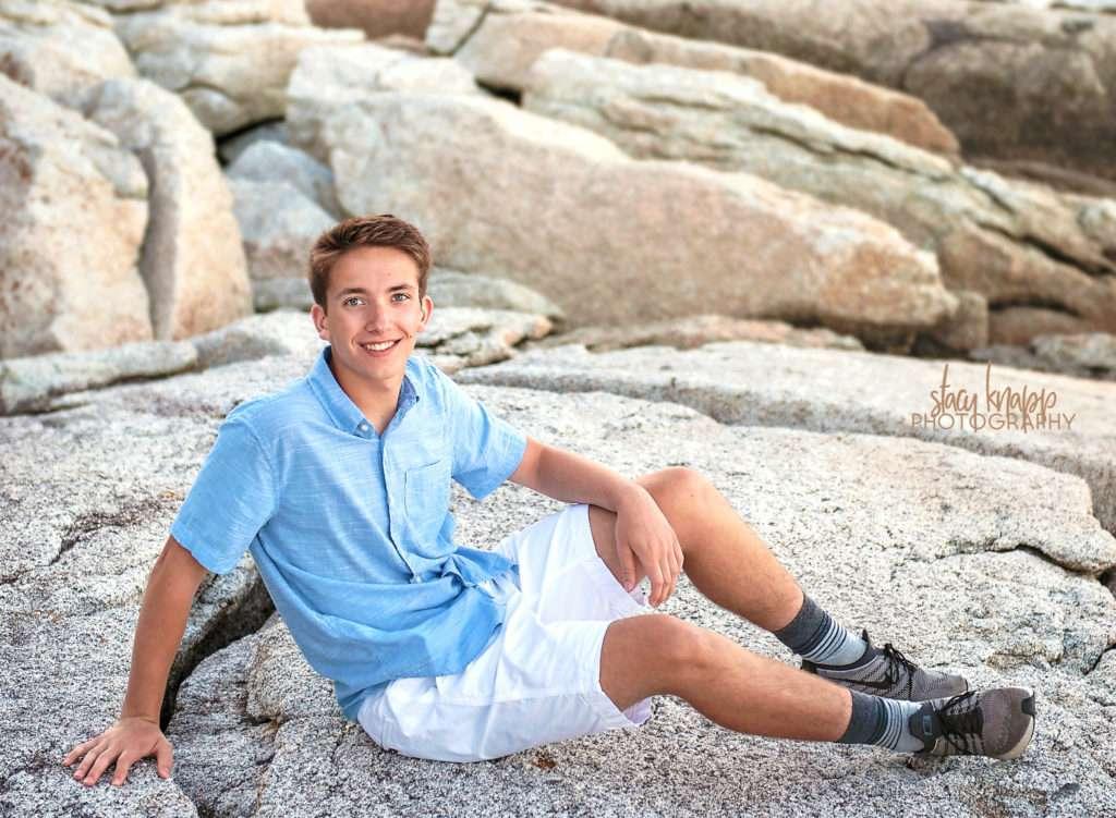 High school senior boy sitting on rocks