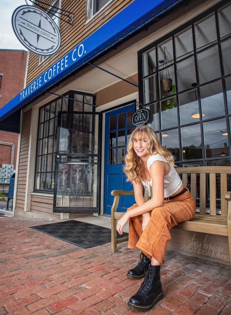High school senior girl sitting outside on bench in front of coffee shop