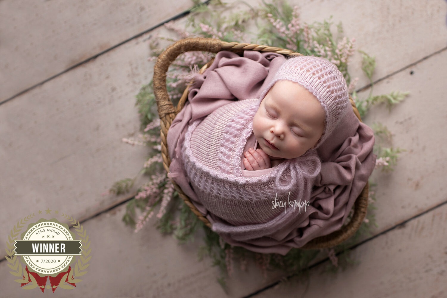 newborn baby wrapped in pink in a basket award winning