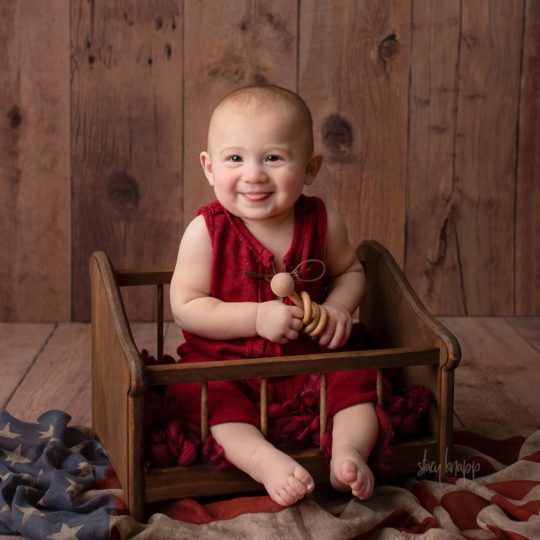 Baby sitter in red outfit with flag on wood background